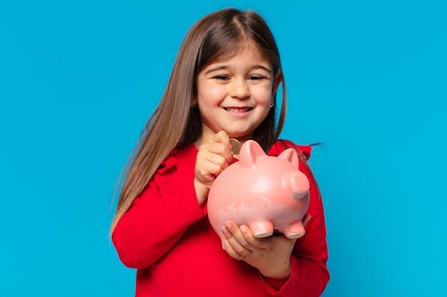 Mooie kleine meisjes gelukkige uitdrukking en houden een spaarvarken