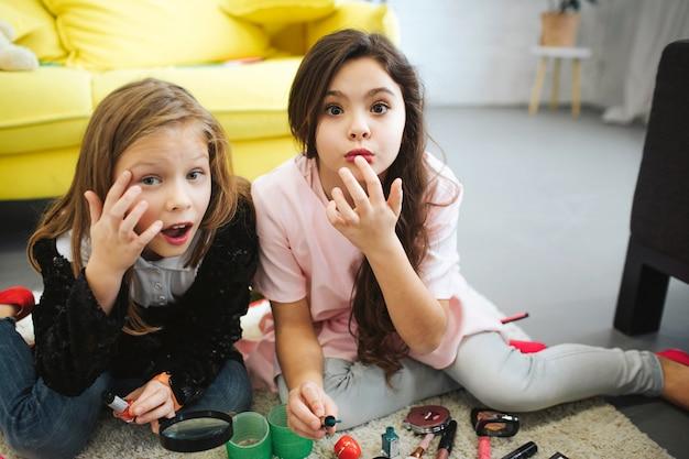 Mooie kleine meisjeszitting op tapijt in ruimte. ze lijken dichtbij. meisjes plaatsen wat schaduw op hun oogleden en lippen.