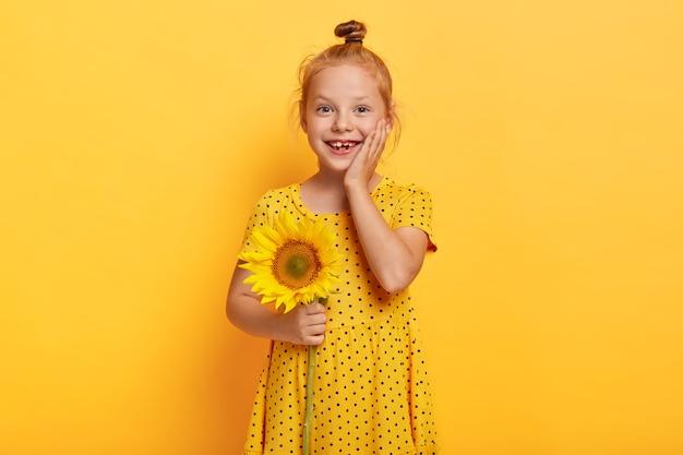Mooie kleine roodharige meisje poseren met zonnebloem in gele jurk