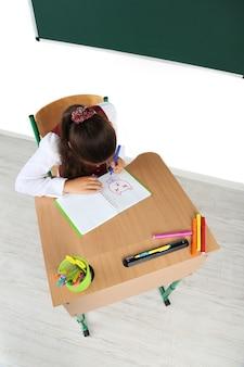 Mooie kleine schoolmeisje in de klas en trekt in notitieblok