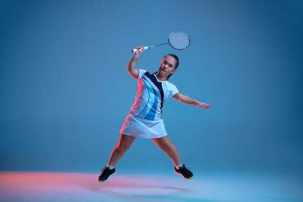 Mooie kleine vrouw die in badminton oefent