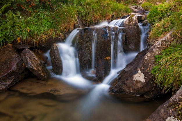 Mooie kleine waterval in bergen met wit schuimend water