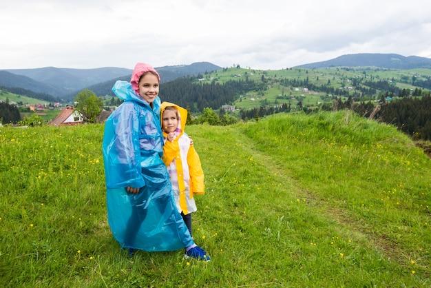 Mooie kleine zusjes in regenjassen lopen rond pittoreske plaatsen met groen gras en bloemen op de achtergrond van bergen en huizen op bewolkte zomerdag. concept van openluchtrecreatie voor kinderen
