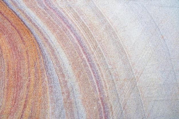 Mooie kleurrijke de textuurachtergrond van de zandsteenmuur.