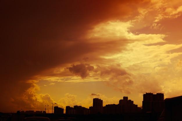 Mooie kleurrijke dramatische zonsonderganghemel met stormachtige wolken over silhouet van de stad