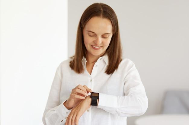 Mooie knappe jonge volwassen vrouw die een wit casual stijl overhemd draagt met behulp van smartwatch, kijkend naar een apparaat met een vrolijke gezichtsuitdrukking, moderne technologie.