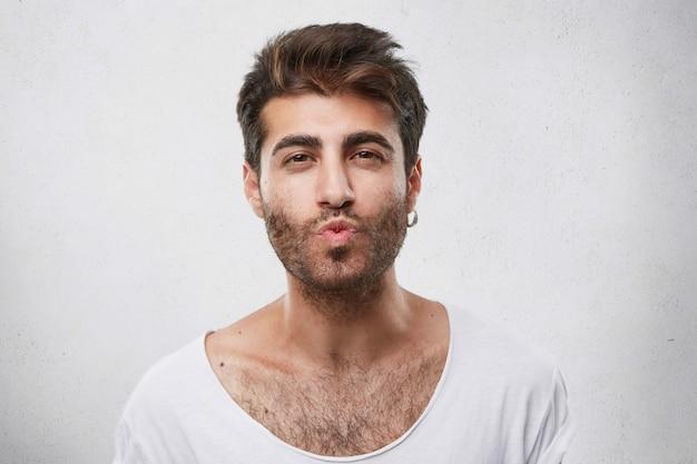 Mooie knappe jongen flirten met meisje blaast haar kus. ongeschoren man met een aantrekkelijk uiterlijk die zijn vriendin medeleven toont die haar gaat kussen. macho man