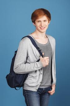 Mooie knappe vrolijke student met gemberhaar in casual outfit lachend, met rugzak en hand in zak, met ontspannen en vrolijke uitdrukking.
