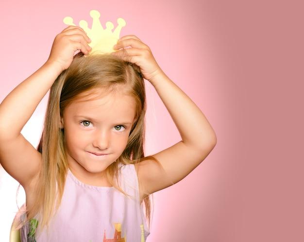 Mooie koningin in gouden kroon. prinsesje meisje in gele kroon en mooie jurk op roze achtergrond.