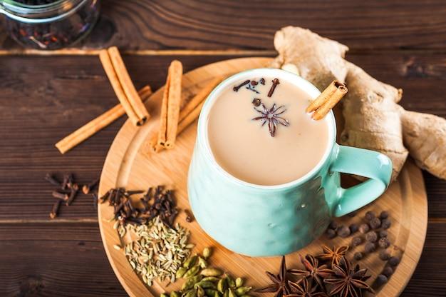 Mooie kop thee met melk, steranijsplant, kaneel op een houten achtergrond.