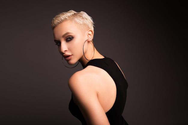 Mooie kortharige blonde op een grijze muur. het meisje met een verdachte blik. het meisje vermoedde en draaide zich om.