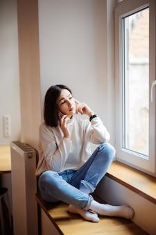 Mooie kortharige dame die in jeans op de vensterbank zitten en bericht op smartphone thuis schrijven
