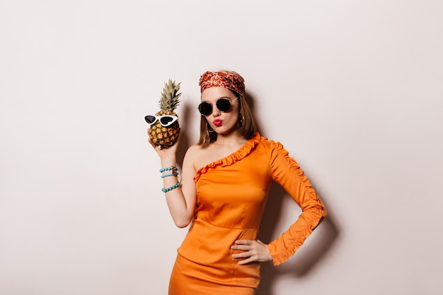 Mooie kortharige vrouw in zonnebril en trendy oranje jurk droeg een bril op ananas.