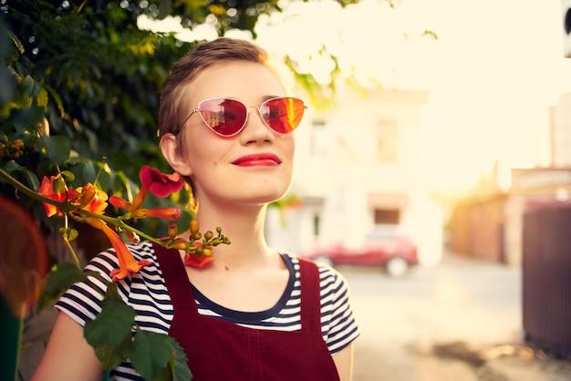 Mooie kortharige vrouw met een zonnebrilstruik met bloemen buitenshuis
