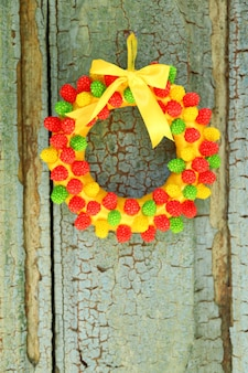 Mooie krans van snoepjes die aan oude houten deur hangen