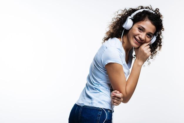 Mooie krullend-haired jonge vrouw die naar de muziek in hoofdtelefoons luistert en gelukkig lacht terwijl naar rechts leunt op grijs