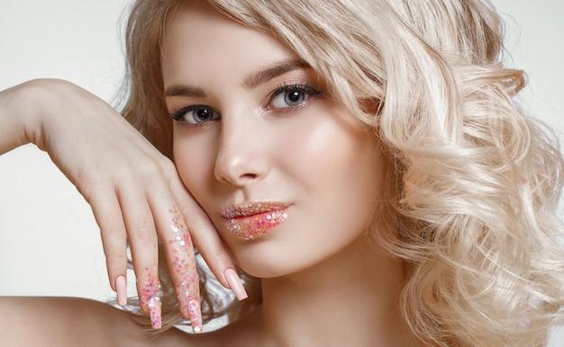 Mooie krullende blonde vrouw met perfecte kunst make-up, trendy berijpt nageldesign met glitter.