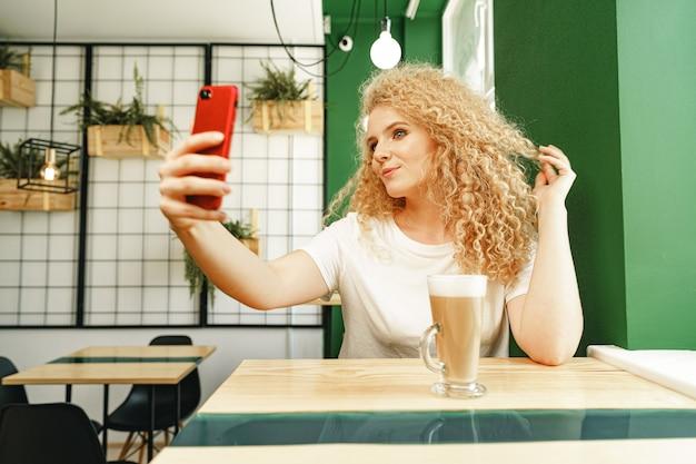 Mooie krullende blonde vrouw selfie te nemen in de coffeeshop