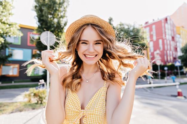 Mooie krullende dame in trendy gele kleding die van de ochtend geniet. buiten foto van vrolijk meisje met plezier in de stad.