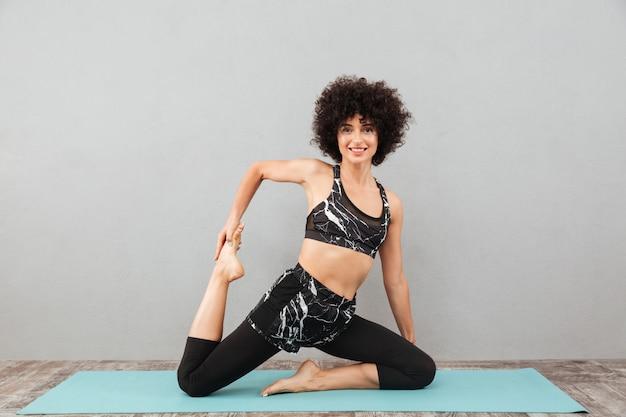 Mooie krullende fitness dame maakt sport yoga-oefeningen