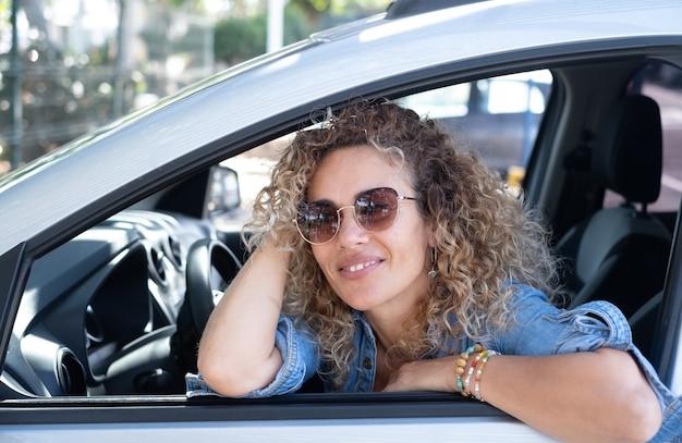 Mooie krullende vrouw in de auto leunend tegen het raam en glimlachend naar buiten kijkend