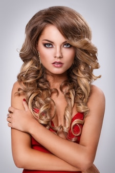 Mooie krullende vrouw in rode jurk