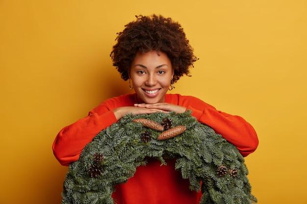 Mooie krullende vrouw leunt op groene krans, gekleed in casual trui, versiert huis voor kerstmis, heeft brede glimlach, geïsoleerd op gele achtergrond.