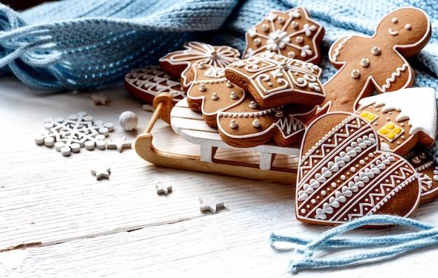 Mooie kunst kerstkoekjes met speelgoed slee en gebreide wollen sjaal op witte houten tafel.