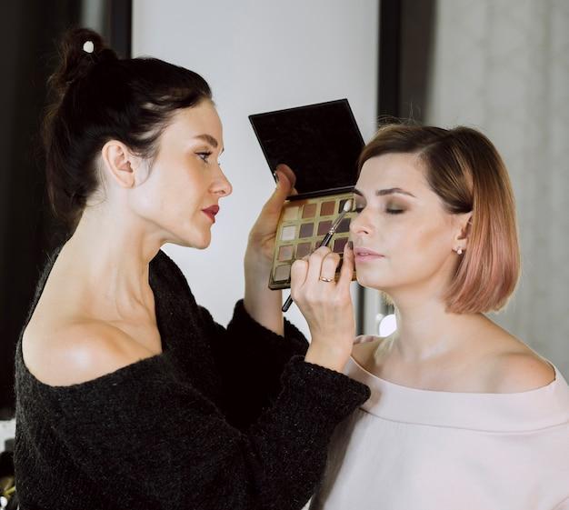 Mooie kunstenaar die make-up op model toepast