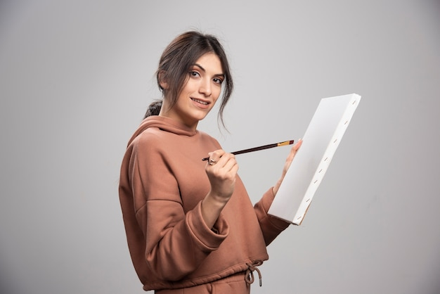 Mooie kunstenaar poseren met kwast en canvas.