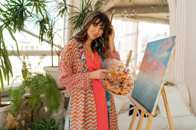 Mooie kunstenaarsvrouw in boheemse outfit poseren met penseel en palet in haar kunststudio.