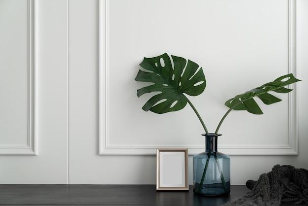 Mooie kunstplant in blauwe glazen vaas met gouden roestvrijstalen frame op zwarte houten tafel in een minimalistisch modern stijl appartement