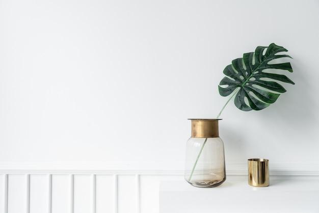 Mooie kunstplant in glazen vaas met gouden roestvrijstalen rand en gouden spiegelvaas op lege open haard in minimalistisch appartement in moderne stijl
