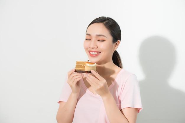 Mooie lachende aziatische jonge vrouw met een chocoladetaart geïsoleerd.