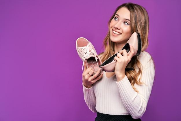 Mooie lachende blonde vrouw met schoenen op een roze muur