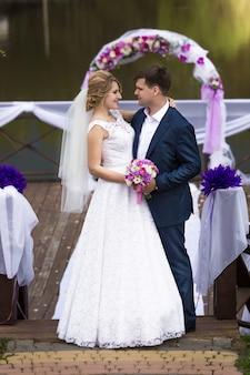 Mooie lachende bruid en bruidegom kijken elkaar onder boog op pier