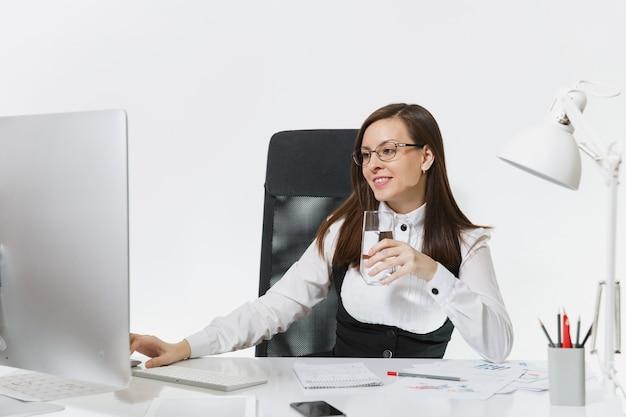 Mooie lachende bruinharige zakenvrouw in pak en bril zitten aan de balie met glas zuiver water, werken op computer met moderne monitor met documenten in licht kantoor