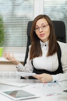 Mooie lachende bruinharige zakenvrouw in pak en bril zitten aan de balie met tablet, werken op de computer met documenten in licht kantoor, schrijven met potloodinformatie naar notebook