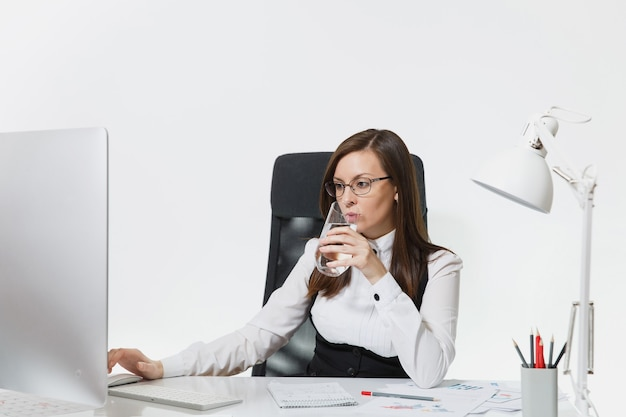 Mooie lachende bruinharige zakenvrouw in pak en bril zitten aan de balie, puur water drinken, werken op computer met moderne monitor met documenten in licht kantoor