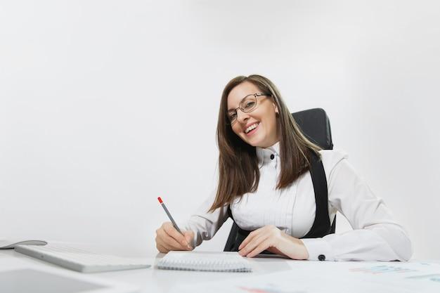 Mooie lachende bruinharige zakenvrouw in pak en bril zitten aan de balie, werken op computer met moderne monitor en documenten in licht kantoor, schrijven in notitieblok