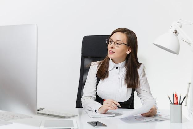 Mooie lachende bruinharige zakenvrouw in pak en bril zitten aan de balie, werken op computer met moderne monitor met documenten in licht kantoor, opzij kijkend