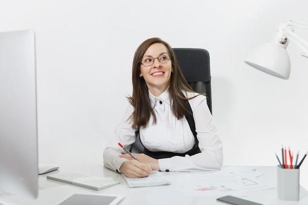 Mooie lachende bruinharige zakenvrouw in pak en bril zitten aan de balie, werken op de computer met moderne monitor met documenten in licht kantoor