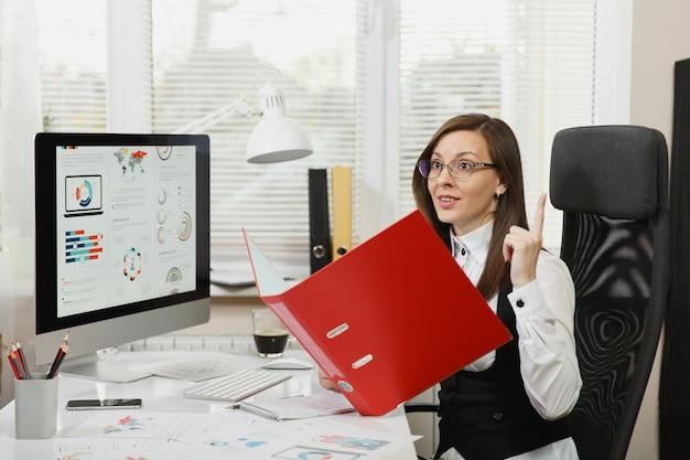 Mooie lachende bruinharige zakenvrouw in zwart-wit pak en bril zittend aan de balie met rode map, mobiele telefoon en kopje koffie, werken op de computer met documenten in licht kantoor.