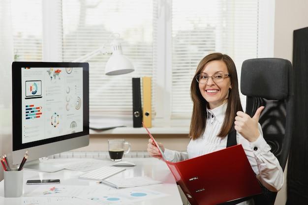 Mooie lachende bruinharige zakenvrouw in zwart wit pak, zittend aan de balie met rode map, mobiele telefoon, kopje koffie, duim opdagen, werken op de computer met documenten in licht kantoor.