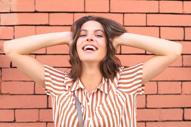 Mooie lachende brunette model gekleed in zomer hipster kleding. grappige en positieve vrouw die plezier heeft.