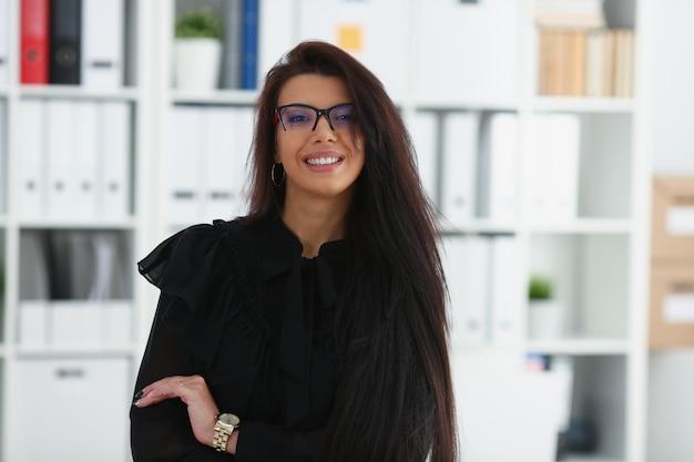 Mooie lachende brunette vrouw in kantoor
