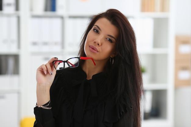 Mooie lachende brunette vrouw met bril in kantoor