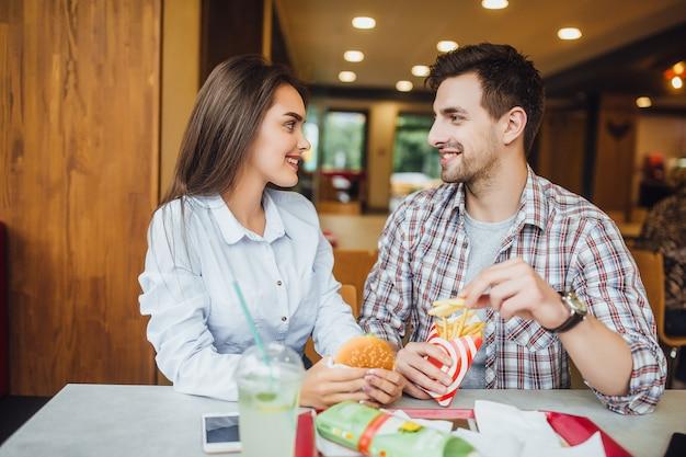 Mooie lachende en jonge vrienden krijgen plezier tijdens het eten van hamburger en frietjes in het snelle restaurant. lifestyle-concept