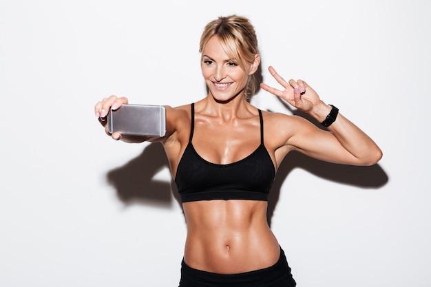 Mooie lachende fit sportvrouw nemen van een selfie