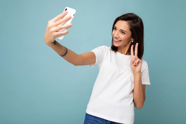 Mooie lachende gelukkige jonge muur vrouw, gekleed in casual wit t-shirt geïsoleerd over